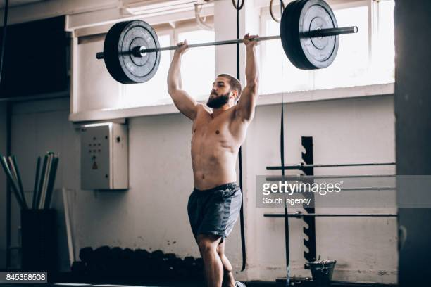 man lifting weights - snatch weightlifting stock photos and pictures