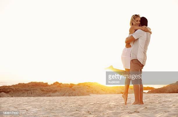 Man lifting woman at beach