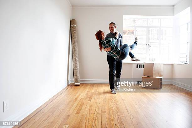Man lifting woman in empty apartment
