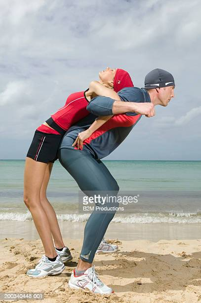Man lifting woman on back on beach, side view