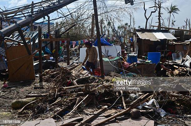 A man lifts a beam to start building his house in Tacloban City on November 14 2013 in Tacloban Philippines Typhoon Haiyan which ripped through...