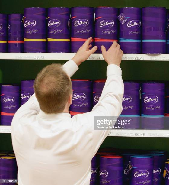 A man lifts a Cadbury Chocolate easter egg from the shelf at the Cadbury World visitor centre on February 25 2005 in Birmingham England The company...