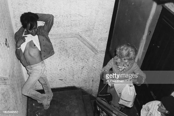 A man lifts his tshirt to expose his chest Lower East Side New York City 1978