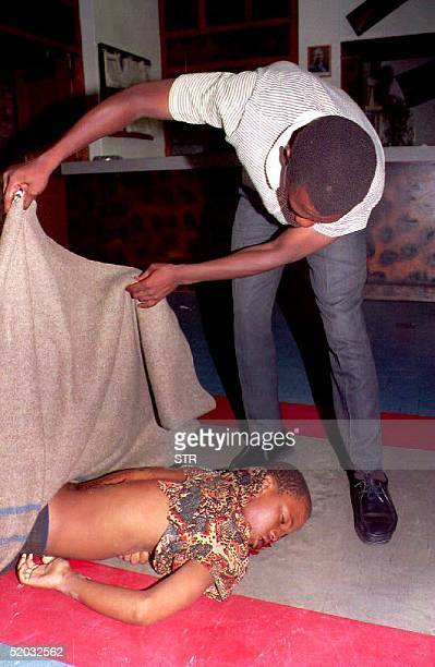A man lifts the blanket covering a thirteenyearold youth allegedly killed by police gunfire in Guguletu township Cape Town South Africa 06 January...