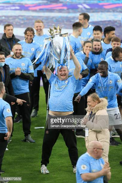 Man lifts the trophy as Benjamin Mendy of Manchester City laughs and smiles as he looks on during the Premier League match between Manchester City...