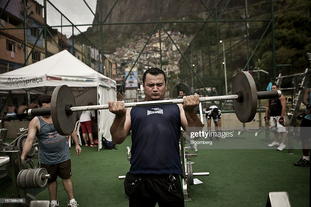 A man lifts weights at an outdoor gym in the Rocinha slum of Rio de Janeiro, Brazil, on Wednesday, Nov. 28, 2012. About 56 percent of the 12 million people who live in slums like Rocinha were considered middle class in 2011, up from 29 percent in 2001, according to a study this year by Instituto Data Popular, a Sao Paulo-based research group. Photographer: Dado Galdieri/Bloomberg via Getty Images