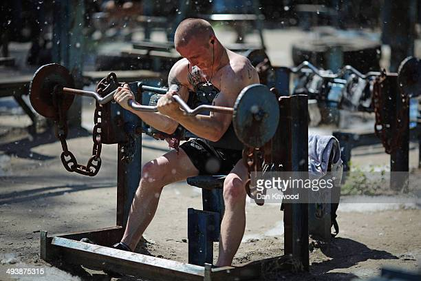 A man lifts weights at Kachalka gym a Soviet era openair fitness area on the island of Tuhev on May 22 2014 in Kiev Ukraine The free park which was...