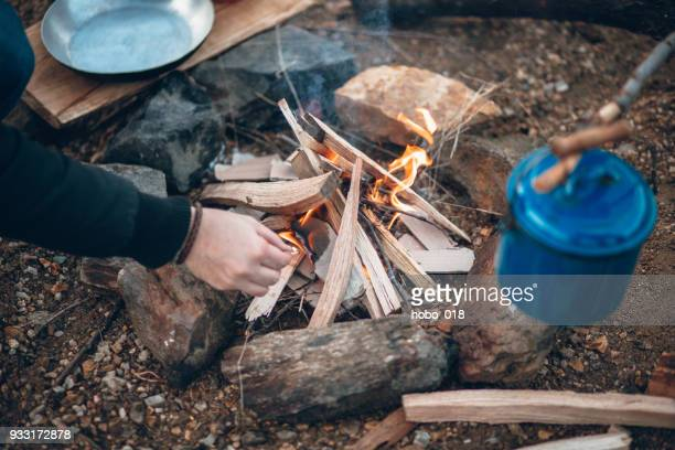 man light camp fire with matches - firewood stock pictures, royalty-free photos & images