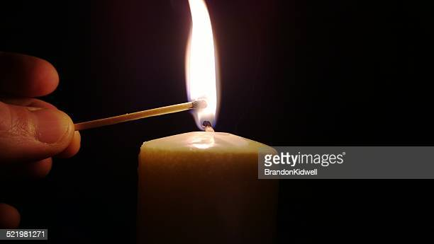 Man lighting a candle with a match