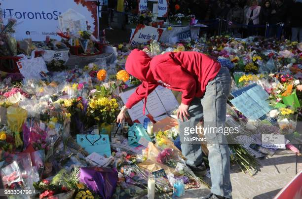Man lighting candles at a memorial during an interfaith vigil at Nathan Phillips Square in memory of the 10 people killed and 15 people injured in a...