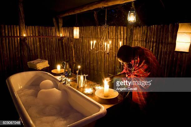 Man Lighting Candles by Bathtub in Safari Camp