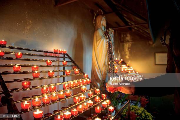 man lighting candles in church - kirche fotografías e imágenes de stock