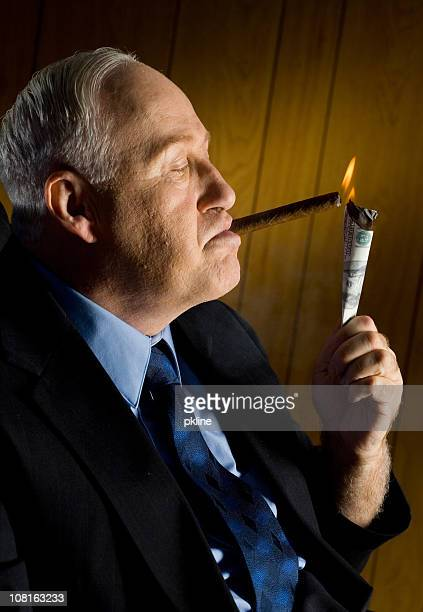 Man lighting cigar with 100 Dollar Bill