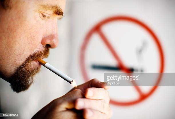 man lighting cigarette in front of no smoking sign - no smoking sign stock pictures, royalty-free photos & images