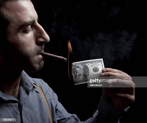 Man lighting up a cigar with US dollar bill