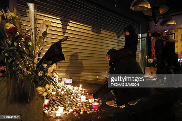 A man lights a candle at a makeshift memorial at Le Belle Equipe restaurant in Paris on November 13 2016 to commemorate the one year anniversary of...