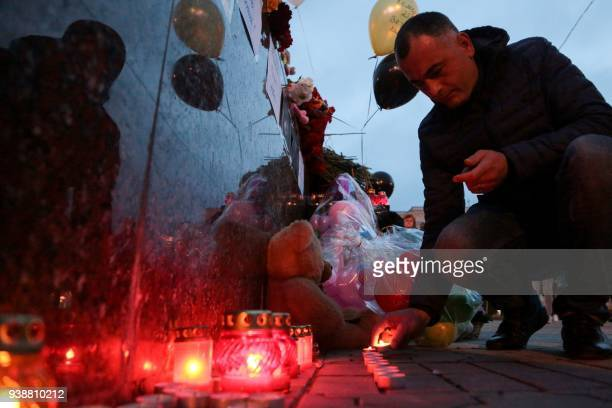 A man lights a candle at a makeshift memorial in tribute to the victims of a Siberian shopping mall fire in Kemerovo in downtown Simferopol on March...