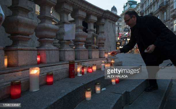 Man lights a candle at the plague column in Vienna's city center on March 25, 2020. - People placed candles as a sign of hope against the corona...