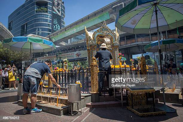 Man lights a candle at the reopened Erawan Shrine in Central Bangkok on August 19th 2015, after a bomb exploded outside this shrine on August 17th,...
