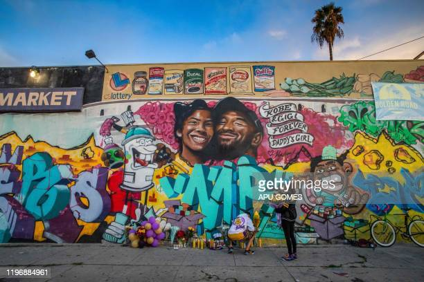 A man lights a candle below a mural by the artists Muck Rock and Mr79lts picturing Kobe Bryant and his daughter Gianna Bryant who were killed with...