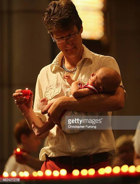 A man lights a candle for the victims of Malaysian Airlines flight MH17 during a special mass in Saint Vitus Church on July 20 2014 in Hilversum...