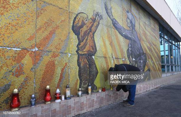 A man lights a candle in front of a mural mosaic at the coal mine in Stonava near Karviná Czech Republic on December 21 where 13 miners died in an...
