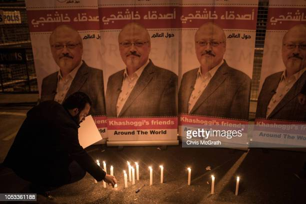A man lights a candle in front of posters of Jamal Khashoggi during a candle light vigil to remember journalist Jamal Khashoggi outside the Saudi...