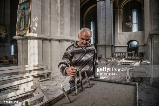 Man lights a candle on October 8, 2020 inside the damaged Ghazanchetsots Cathedral in the historic city of Shusha, some 15 kilometers from the...