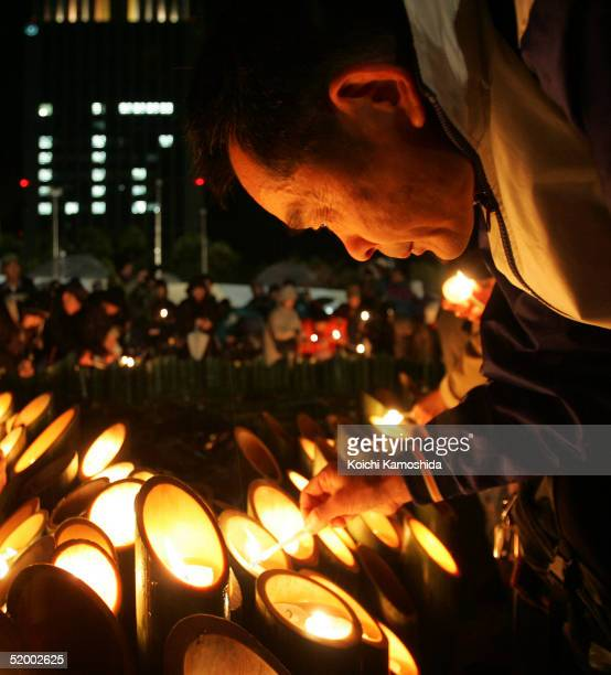 A man lights a candle to offer prayers for victims during a memorial service to commemorate the 10th anniversary of the 1995 earthquake in Kobe on...
