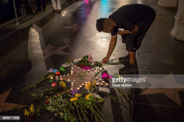 A man lights a cigarette from a candle on the Tom Petty and the Heartbreakers star on The Hollywood Walk of Fame on October 2 2017 in Los Angeles...