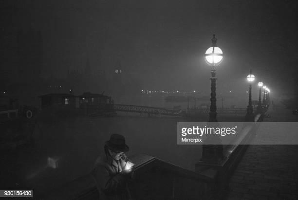 Man lights a cigarette on the Thames Embankment at night. Circa 1955.