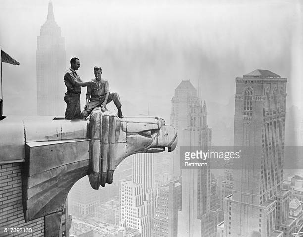 A man lights a fellow worker's cigarette as they take a break on a Chrysler Building gargoyle