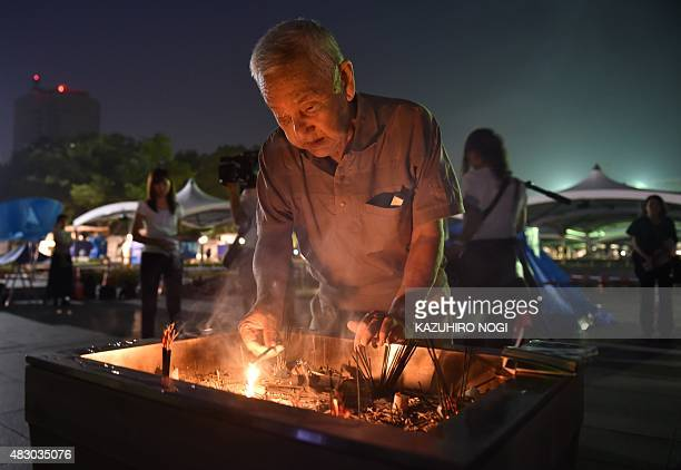 A man lights a fire in the incense to pray for the victims of the 1945 atomic bombing at the Peace Memorial Park in Hiroshima on August 6 2015 Japan...