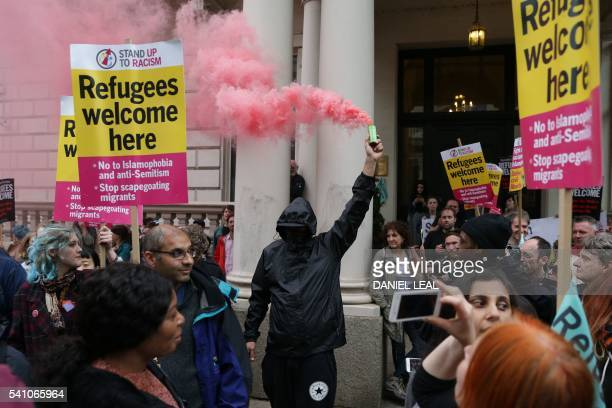 A man lights a flare among prorefugee activists rallying outside the French Embassy in central London on June 18 2016 during a protest after most of...