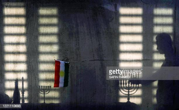Man lights a menorah as a Kurdish flag is seen nearby while members of an Iraqi Kurdish Jewish family gather for Shabbat prayer service at their home...