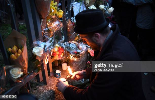 A man lights candles as he gathers with others at the entrance to an apartment building in Paris on March 28 at the conclusion of a march in memory...