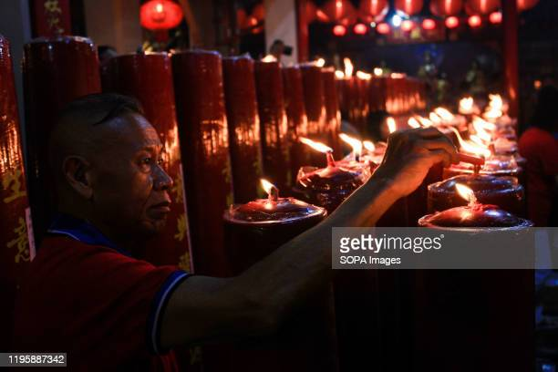 A man lights candles during the celebration at Dharma Ramsi Temple in Bandung Hundreds of candles are lit at midnight and Prayers for the 2571...