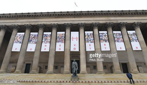 A man lights candles in 96 lanterns arranged on the steps of St Georges Hall in Liverpool northwest England on April 15 2019 to commemorate the 30th...