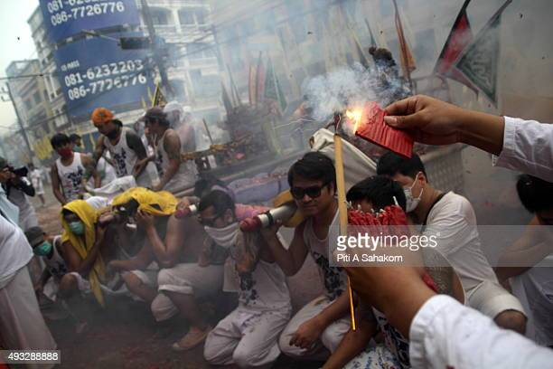 A man lights firecrackers over devotees of a Chinese shrine carrying an idol on a palanquin during a street procession in Phuket Vegetarian Festival...