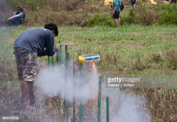 A man lights fireworks launch as a gesture to god for the sake of the rainy season during the Ban Bung Fai Rocket Festival in Yasothon Thailand