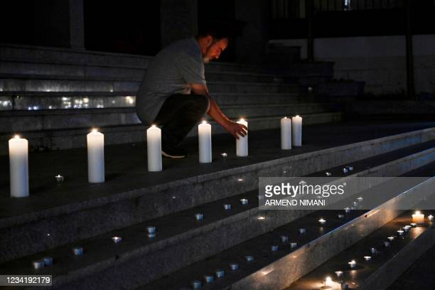 Man lights up a candle in Pristina on July 25, 2021 to pay tribute for the Kosovo Albanian victims who died in a bus crash in Croatia. - Ten people...