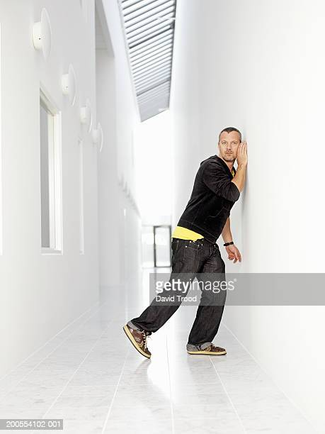 man listening at wall, side view - leaning stock pictures, royalty-free photos & images