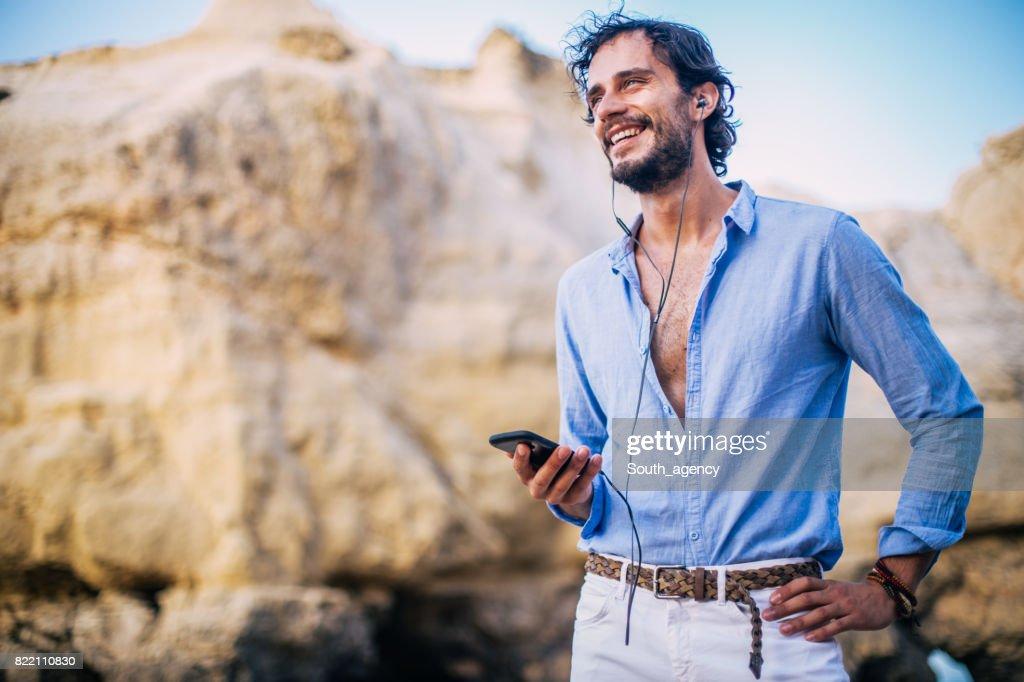 Man listening music at coastline : Stock Photo