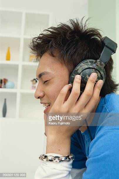 Man listening music, eyes closed, side view