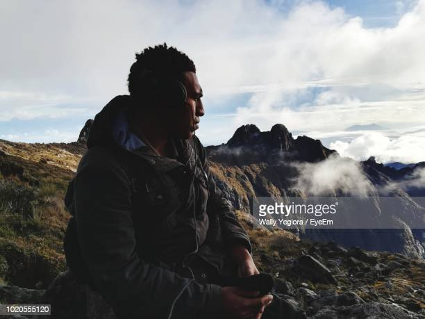 man listening music on mountain against sky - wally yegiora stock photos and pictures