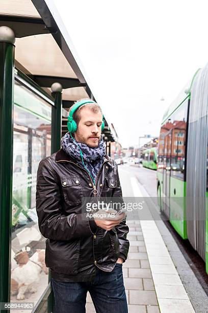 Man listening music through mobile phone while waiting at bus stop