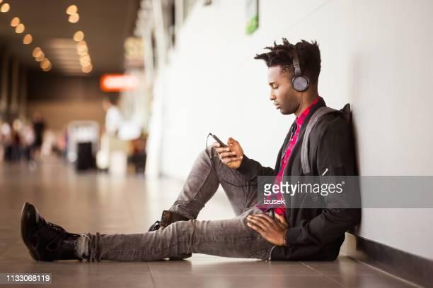 man listening music through smart phone at airport - izusek imagens e fotografias de stock