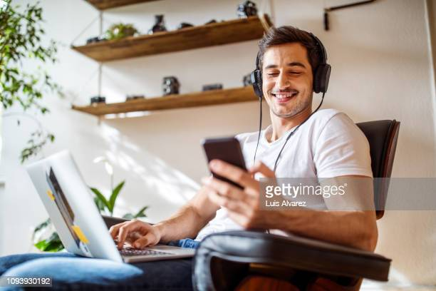 man listening music while working on laptop - upload stock pictures, royalty-free photos & images