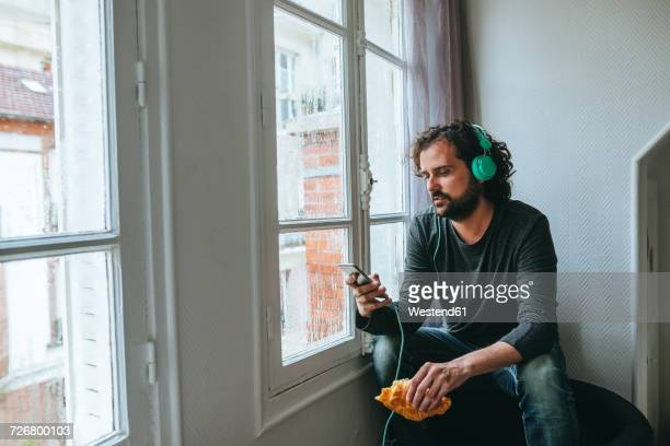 Man listening music with headphones and smartphone at home