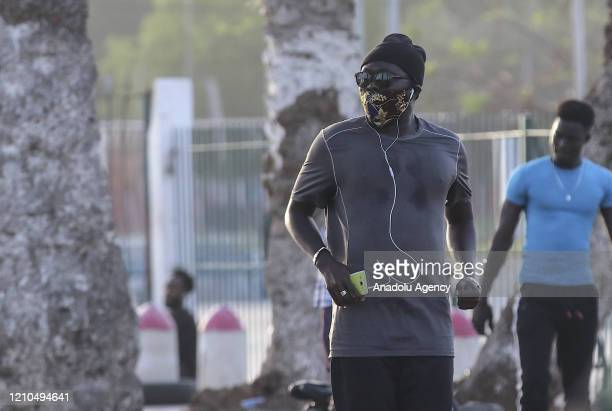 Man listening music with his headphones is seen walking around a street as a precaution against the new type of coronavirus in Dakar, Senegal on...